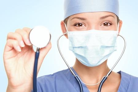 quirurgico: Joven m�dico  cirujano mostrando estetoscopio con m�scara de cirujano mirando c�mara. Asia  cauc�sico modelo femenino.  Foto de archivo