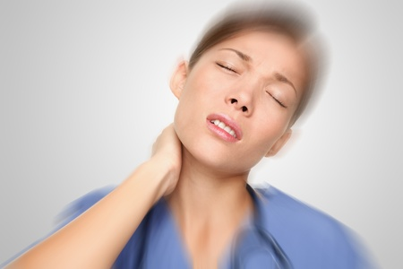 shoulder pain: Nurse or young woman doctor having neck and back pain problems at work. Mixed-race Asian  Caucasian female model. Stock Photo