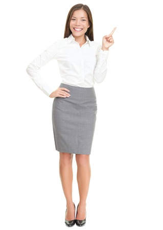 presenting: Woman pointing on white standing in full length. Caucasian  Asian woman smiling. Isolated over white background.