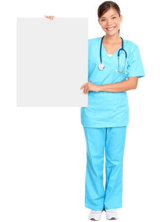 Medical doctor showing blank empty billboard sign poster. Young female doctor  nurse standing in full body isolated over white background. Asian  Caucasian woman. photo