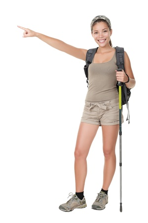 backpacking: Hiker woman standing isolated. Female hiker pointing. Young woman wearing backpacking bag and hiking poles. Isolated on white background in full length. Stock Photo