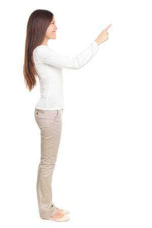 side pose: Isolated woman pointing or pushing something with index finger. Beautiful casual young woman isolated on white background in full length standing in profile. Stock Photo