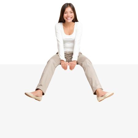 Jolie fille assise décontractée sur grand panneau d'affichage panneau blanc avec beaucoup de copie espace. Sourire asiatique caucasien jeune femme modèle. Isolé sur fond blanc
