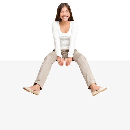 sitting chair: Pretty girl sitting casual on big blank billboard poster sign with lot of copy space. Smiling asian caucasian young woman model. Isolated on white background Stock Photo