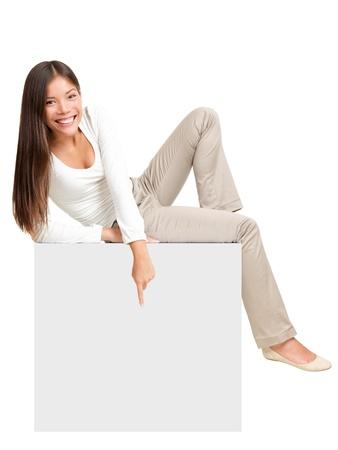 mujer sentada: Mujer que se sienta en el cartel de papel vacío en blanco, apuntando hacia abajo en copia espacio. Imagen de cuerpo entero de la mujer ocasional lindo en blanco aislado en fondo blanco.