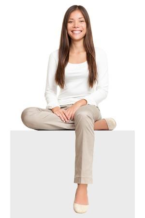 persona sentada: Personas de signo. Mujer sentada en signo de cartel de billboard en blanco. Young casual hermoso asi�tico multirracial aisladas sobre fondo blanco. Foto de archivo
