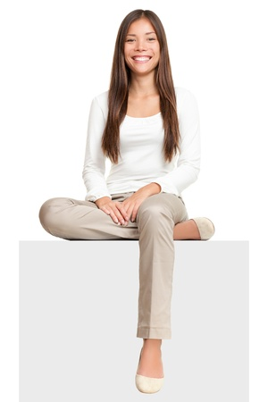 sitting on: Sign people. Woman sitting on blank billboard placard sign. Casual young beautiful multiracial Asian isolated on white background. Stock Photo