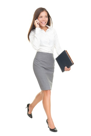 person walking: Businesswoman walking talking on mobile phone. Young stylish business woman smiling isolated on white in full body. Mixed-race chinese asian  white caucasian brunette female model.