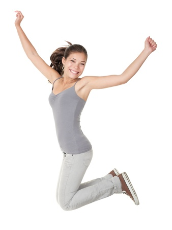 Jumping people isolated on white background: casual woman jumping happy and free in full body. Beautiful Caucasian Asian model smiling. photo