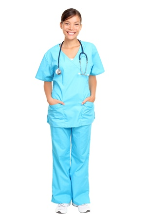 Nurse standing isolated. Young multiracial nurse or medical doctor standing isolated in full length wearing blue scrubs. photo