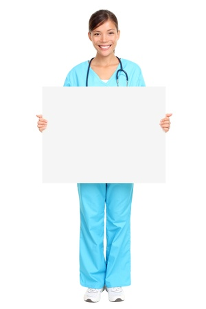 placard: Nurse showing medical sign billboard standing in full length. Young smiling nurse or doctor in scrubs showing empty blank sign board with copy space. Asian Caucasian female model isolated on white background.