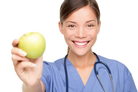 nutritionist: Nurse or young doctor giving an apple smiling. Health care concept isolated on white background. Stock Photo