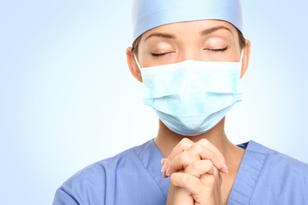 Doctor praying for help. Young woman medical doctor surgeon or nurse portrait. Stock Photo - 8828853