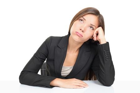 agotado: Aburrido de empresarios: mujer sentada en la mesa mirando hacia arriba aburrido. Mujer de hermosa joven multi�tnica asi�tica del C�ucaso businss aislada sobre fondo blanco. Foto de archivo