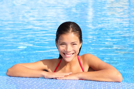 sun bathing: Beautiful natural woman smiling in pool on summer vacations. Gorgeous multi ethnic Asian Caucasian young female model in bikini.