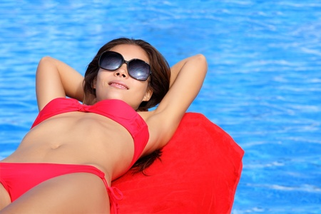 swimming suit: Sunbathing woman by pool on summer holidays. Natural beautiful multiracial Asian Caucasian young female model in bikini Stock Photo