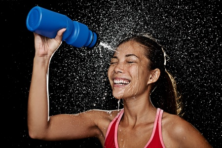 spraying: Woman fitness runner drinking and splashing water in her face. Funny image of beautiful female fitness model on black background. Stock Photo