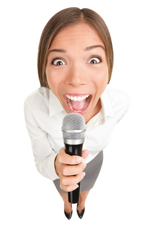 Businesswoman screaming  talking in microphone. Funny photo of young casual business woman holding microphone. Asian Caucasian female model isolated on white background. photo