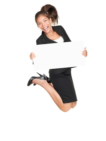 cheer full: Sign businesswoman jumping happy and excited showing blank empty sign board with copy space for text. Pretty young asian caucasian woman isolated on white background in full length. Stock Photo