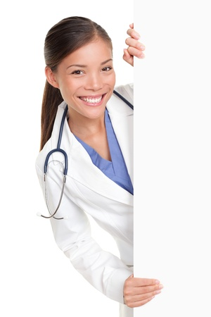 displaying: Medical doctor showing billboard sign empty with copy space for text. Beautiful mixed race Chinese Asian  white Caucasian female nurse or young medical professional isolated on white background.