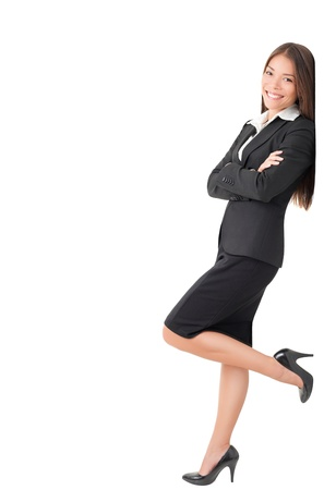 skirt suit: Businesswoman in suit leaning on wall. Young Caucasian Asian professional woman isolated on white background