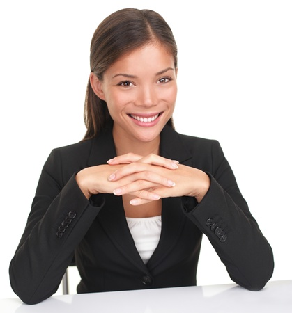 Business woman sitting at table smiling with hands folded. Young Caucasian Asian professional woman isolated on white background. photo