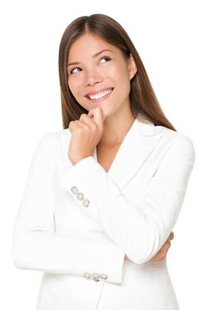 mujer pensando: Mujer de negocios de pensamiento sonrientes mirando espacio de copia. Hermosa joven profesional aislada sobre fondo blanco.
