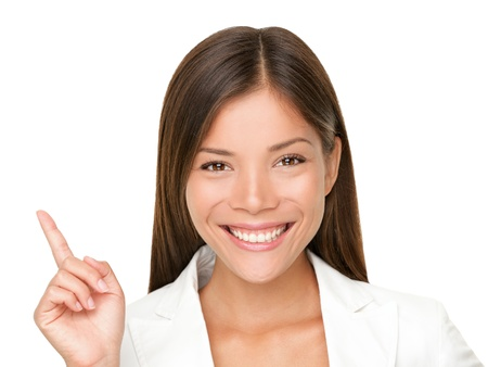 pointing up: Woman smiling pointing up showing copy space. Closeup of beautiful young professional businesswoman isolated on white background.