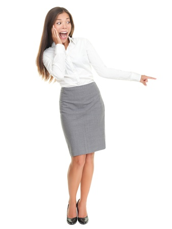 surprised: Surprised woman pointing. Pretty businesswoman standing in full length isolated on white background.
