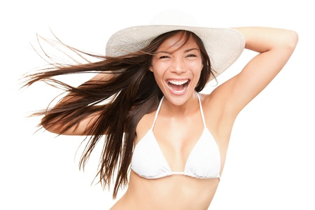 hot asian: Summer bikini woman isolated in studio. Very energetic fresh portrait of young woman smiling in white bikini and beach hat. Beautiful mixed race Asian Caucasian model isolated on white background.