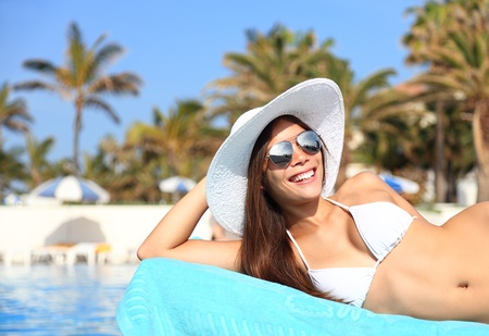 lounger: Woman sunbathing in bikini at tropical travel resort. Beautiful young Asian Caucasian woman smiling lying on sun lounger near pool.