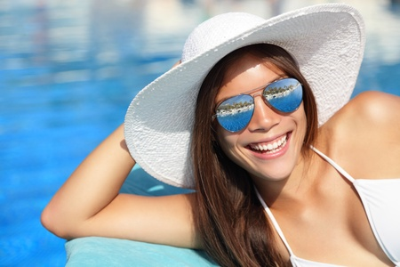 Summer bikini girl smiling by pool. Beautiful young woman wearing beach hat and sunglasses at tropical resort. Beautiful Asian Caucasian female model. photo