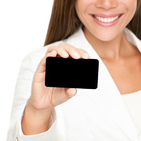 holding business card: Woman showing business card. Young female professional executive smiling in white suit - closeup of business card.