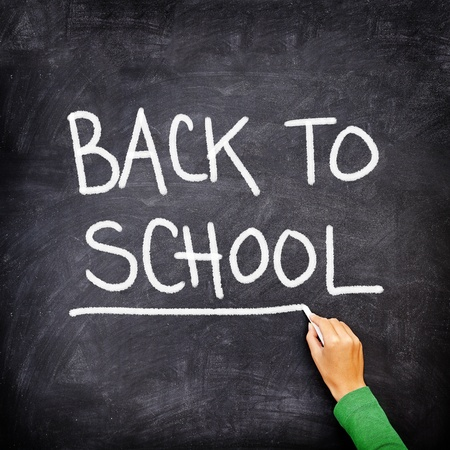 Back to school blackboard / chalkboard. Teacher writing back to school on black chalk board. Stock Photo - 9416221