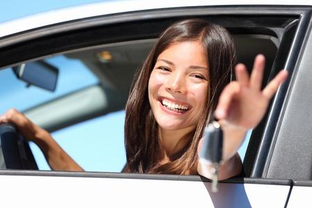 conducci�n: Mujer mostrando llaves de conducci�n por la ventana. Hembra joven feliz con su nuevo coche o controladores de permiso de conducci�n. Controlador de raza mixta hermosa cauc�sica  Asia.