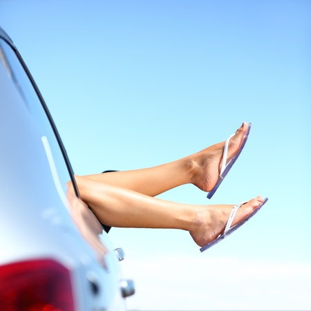 Summer road trip car vacation concept. Woman legs out the windows in car above the clouds. Conceptual freedom, travel and holidays image with copy space. photo