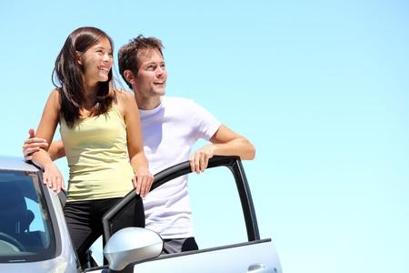 Couple heureux avec la voiture. Jeune couple interracial debout avec la voiture en regardant le ciel avec copie espace.