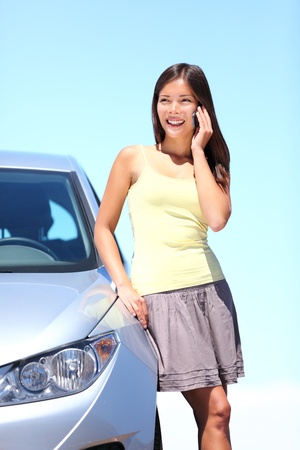 calling on phone: Young woman standing by car talking on mobile phone. Happy smiling mixed race Caucasian Asian woman on a beautiful bright sunny summer day.