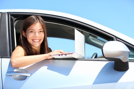 Laptop woman in car on internet outside. Smiling young woman using computer netbook outdoors. Asian Caucasian female professional. photo