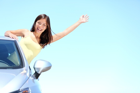 Car woman on road on road trip waving happy smiling out the window. Asian Caucasian girl on summer holidays above the clouds. Stock Photo - 9493420