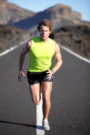 sudando: Ejecutando atleta de hombre en camino al aire libre. Ajuste el hombre de corredor de gimnasio en ejecución y sudoración en paisaje áspero. Imagen de cuerpo completo de joven caucásica muscular. Foto de archivo