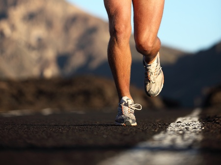 Sport running shoes in action. Closeup of male runner legs and sports shoes. Fitness man running on mountain road.