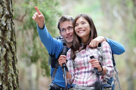 hiking stick: Happy couple hiking outdoors in forest. Active young asian woman hiker and caucasian man. Stock Photo