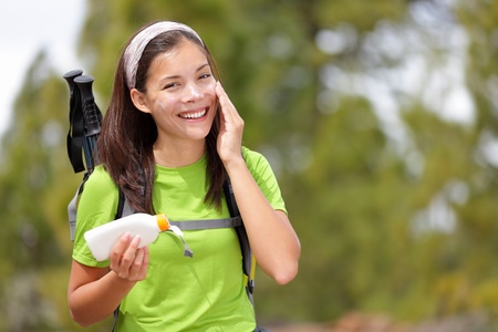 sunblock: Hiker sunscreen. Woman hiking putting sun block lotion outdoors during summer hike holidays. Mixed race Caucasian Asian female model.