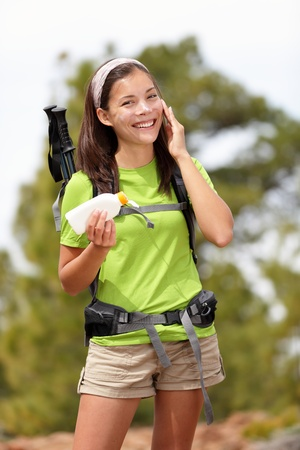 Sunscreen lotion woman. Woman hiking putting sun block lotion outside during summer hike vacation. Asian Caucasian female model. photo
