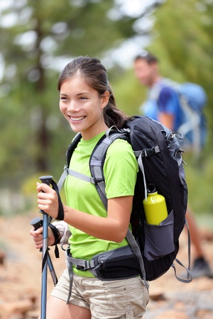 Hiking woman happy outdoors on hike in forest. Hiker in the background. Sporty active Asian Caucasian mixed race young woman smiling holding hiking sticks. Tenerife, Canary Islands, Spain photo