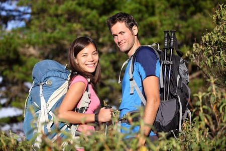 Happy hiking couple smiling during hike in forest on Tenerife, Canary Islands, Spain. Mixed race couple. photo
