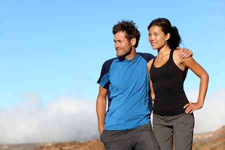 happy couple looking outdoors. Sporty healthy young interracial couple looking at blue sky smiling. Asian woman and Caucuasian man on Teide, Tenerife, Spain. photo