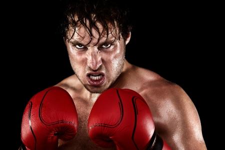 Boxer boksen staren boos, betekenen en zweet weergegeven: sterkte. Jonge man op zoek agressief met bokshandschoenen. Kaukasische mannelijk model geïsoleerd op zwarte achtergrond. Stockfoto