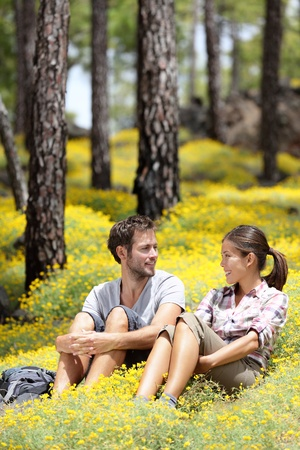 Happy couple in forest sitting smiling around flowers. Beautiful young couple: Asian woman, Caucasian man. Photo from Tenerife, Spain. photo